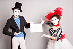 Your text here. Actors mimes holding empty blank board. Colorful studio portrait with gray background. April fools day Stock Images