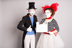 Your text here. Actors mimes holding empty blank board. Colorful studio portrait with gray background. April fools day Royalty Free Stock Photography