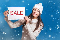 Your text here. Pretty young happy woman in winter clothes holding empty blank board. Colorful studio portrait with blue backgroun Stock Images