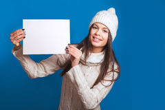 Your text here. Pretty young happy woman in winter clothes holding empty blank board. Colorful studio portrait with blue backgroun Stock Photos