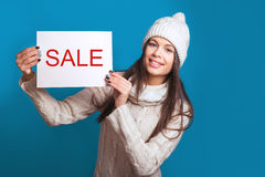 Your text here. Pretty young happy woman in winter clothes holding empty blank board. Colorful studio portrait with blue backgroun Royalty Free Stock Photos