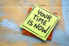 Your time is now - reminder note. Your time is now reminder - handwriting on a sticky note against grunge wood stock photo