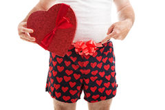 Your Valentines Day Gift. Guy in his underwear with a Valentines Day gift and a bow around his underwear, pointing toward his crotch. Isolated on white stock photo