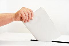 Your vote matters. Close up of a woman's hand putting her vote in the ballot box Stock Photos