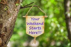 Your weekend Starts Here on Paper Scroll. Hanging from the tree with nature green bokeh light background stock image