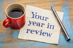 Your year in review napkin concept. Your year in review - handwriting on a napkin with a cup of espresso coffee royalty free stock photography