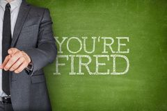 Youre fired on blackboard. With businessman finger pointing Royalty Free Stock Images