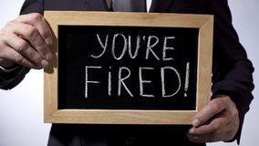 Youre fired with exclamation written on blackboard, businessman holding sign stock photos