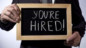 Youre hired with exclamation written on blackboard, businessman holding sign. Stock footage Royalty Free Stock Images