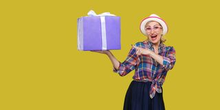 It is yours? Happy beautiful modern grandma in white hat and in checkered shirt standing, surprised holding big gift box with
