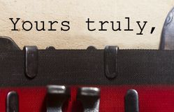 Yours truly typed on an old vintage paper. With od typewriter font Royalty Free Stock Image