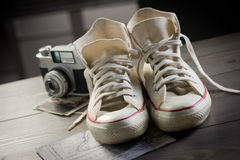 Youth adventure trip. Canvas shoes with vintage camera and world map, youth adventure trip concept Royalty Free Stock Images