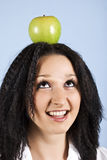 Youth with apple on her head. Youth female standing with an green apple on her head in profile,smiling and looking up  on blue background,check also my Stock Image