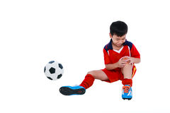Youth asian soccer player with pain in knee joint. Full body. Sports injure. Youth asian soccer player with football in red uniform injured at knee. Isolated on Royalty Free Stock Photos