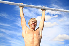 The youth athlete on the crossbeam. Youth athlete pulls on the crossbeam in the open air in summer Stock Photos