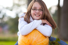 Youth autumn girl smiling. Portrait of a youth girl leaning on a pumpkin Royalty Free Stock Photo