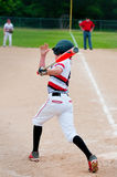 Youth baseball batter swinging bat. Teenage american baseball player swinging bat to hit the ball Royalty Free Stock Photography