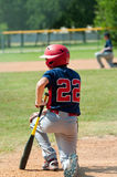 Youth baseball boy kneeling while someone injured. Young baseball player up at bat, kneeling while someone is injured on the field Royalty Free Stock Photos