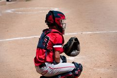 Youth baseball catcher behind home plate. American youth baseball catcher behind home plate waiting on pitch royalty free stock image
