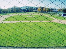 Youth baseball field viewed from behind net stock photos