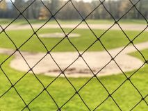 Youth baseball field viewed from behind net stock photography