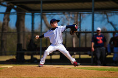 Youth baseball pitcher in wind up. Wearing white jersey Royalty Free Stock Images