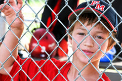 Youth baseball player in dugout. Upclose shot of a Little league baseball player standing in the dugout behind fence Royalty Free Stock Image