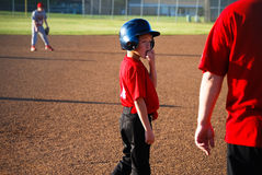 Baseball boy looking at coach royalty free stock photography