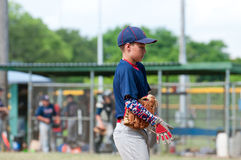 Youth baseball player walking off the field during game. Stock Photography
