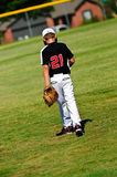 Youth baseball player walking on field Stock Image