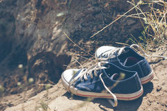 Youth blue sneakers on earth.  Stock Photo