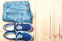 Youth blue sneakers  and  jeans  on wooden background with copy spase Stock Photo