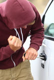 Youth breaking into a car. Youth wearing a hoodie breaking into a car by destroying the door lock with a screw driver Royalty Free Stock Photography