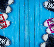 Youth colored sneakers on a blue background of the wooden planks stock photo