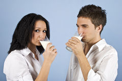 Youth couple drinking milk. Youth couple standing face to face and drinking milk,female looking you on blue background,check also my collection Healthy life Stock Images