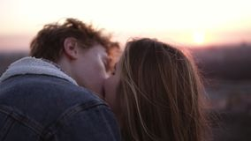 Youth couple enjoying a romantic kiss while standing on the windy high roof with an urban background. Cityscape view.  stock video