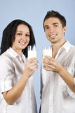Youth couple with milk. Happy youth couple standing together in front of image and holding glasses with milk on blue background,check also my collection Healthy Royalty Free Stock Photography