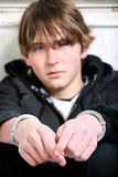 Youth crime. Teenage in handcuffs against wall. Focus on handcuffs stock images