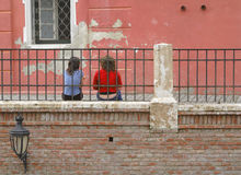 Youth culture. Two teenagers talking near old traditional buildings from Sibiu,Romania.20m to the right there is a very specific bridge called Liers bridge Royalty Free Stock Photography