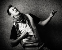 Youth Culture. Black and white image of a young man playing on a invisible guitar.High contrast and grain was added stock photography