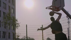Young man scored a ball in basketball hoop outdoor. Youth culture friendly with sport and healthy lifestyle. Pursuit to ambitions, practicing outdoor. Teenager stock video footage