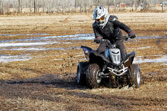 Youth doing donuts in the mud on his quad Royalty Free Stock Photos