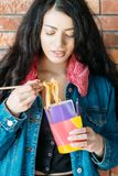 Youth eating habit female chinese noodles yummy. Youth eating habit. Takeout food. Beautiful female millennial with Chinese noodles. Yummy spicy meal, unhealthy stock photography