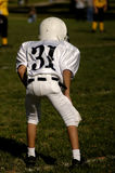Youth football. A young boy huddles down during a youth football game Stock Photography
