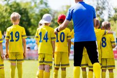 Youth football coach talking to children soccer team. Sports coaching stock photos