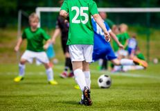 Youth Football Soccer Match. Boys Kicking Soccer Ball. Young Soccer Player Back. Football Kick in the Background stock photos