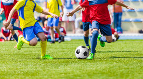 Youth football soccer match. Kids playing soccer game on sport field. Boys kicking football match on pitch. Sports soccer background Royalty Free Stock Images