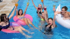 Friends youth swims on inflatable rings into swimming pool with colored beverages on summer holiday. Youth friends swims on inflatable rings into swimming pool stock video footage