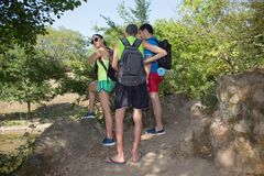 Youth group tourists sightseeing in the woods with backpack, vacation travel Stock Photo