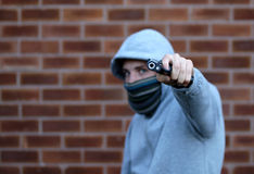 Youth Gun Crime. Youth with hoody pointing handgun in urban setting stock photo